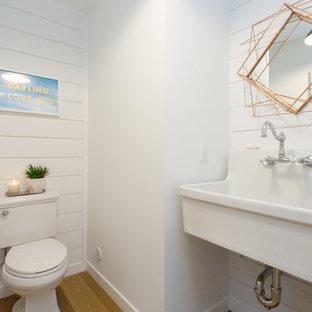 Immagine di un piccolo bagno di servizio costiero con pareti bianche, lavabo sospeso, WC a due pezzi, pavimento in legno massello medio e pavimento arancione