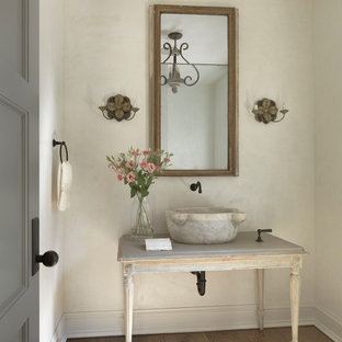 Photo of a traditional powder room in St Louis with furniture-like cabinets, distressed cabinets, beige walls, medium hardwood floors, a vessel sink and brown floor.
