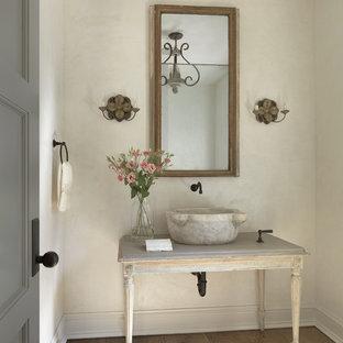 Cette image montre un WC et toilettes style shabby chic avec un placard en trompe-l'oeil, des portes de placard en bois vieilli, un mur beige, un sol en bois brun, une vasque et un sol marron.