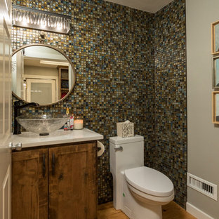 Inspiration for a small classic cloakroom in Dallas with recessed-panel cabinets, medium wood cabinets, a one-piece toilet, multi-coloured tiles, glass tiles, beige walls, medium hardwood flooring, a vessel sink, engineered stone worktops, brown floors and yellow worktops.
