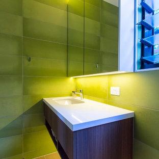 Новые идеи обустройства дома: туалет среднего размера с унитазом-моноблоком, зеленой плиткой, керамической плиткой, зелеными стенами, светлым паркетным полом, врезной раковиной и столешницей из искусственного кварца