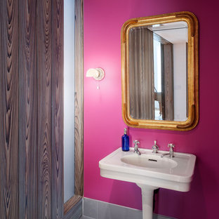 Стильный дизайн: туалет среднего размера в современном стиле с розовыми стенами, раковиной с пьедесталом, серым полом, полом из цементной плитки и столешницей из искусственного камня - последний тренд