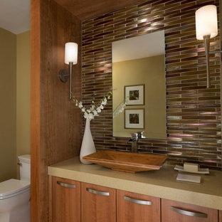 Пример оригинального дизайна: туалет среднего размера в современном стиле с настольной раковиной, плоскими фасадами, фасадами цвета дерева среднего тона, стеклянной плиткой, коричневыми стенами, светлым паркетным полом, столешницей из искусственного кварца и коричневой столешницей