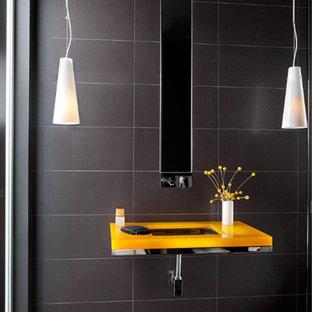 Cette image montre un petit WC et toilettes minimaliste avec un carrelage noir, des carreaux de porcelaine, un mur noir, un sol en carrelage de porcelaine, un lavabo encastré, un sol noir et un plan de toilette jaune.