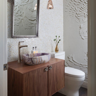 Design ideas for a medium sized traditional cloakroom in Denver with flat-panel cabinets, medium wood cabinets, a one-piece toilet, multi-coloured tiles, glass tiles, white walls, medium hardwood flooring, a vessel sink, wooden worktops, grey floors and beige worktops.