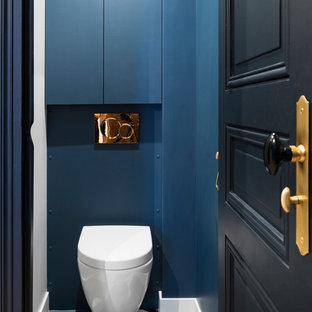 Exemple d'un petit WC et toilettes tendance avec un mur bleu, un carrelage bleu, un sol multicolore, un WC suspendu et un sol en carreaux de ciment.