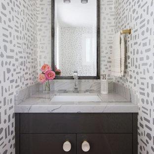 Idée de décoration pour un petit WC et toilettes design avec un placard à porte plane, des portes de placard grises, un mur blanc, un sol en bois brun, un lavabo encastré, un plan de toilette en marbre, un plan de toilette gris et meuble-lavabo encastré.
