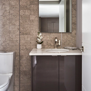 Powder room - contemporary gray tile powder room idea in Chicago with flat-panel cabinets, gray cabinets, a two-piece toilet, gray walls, an undermount sink and white countertops