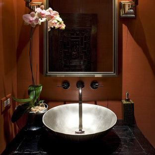 This is an example of a small world-inspired cloakroom in Chicago with a vessel sink, freestanding cabinets, black cabinets, a one-piece toilet, beige tiles, red walls, marble flooring, wooden worktops and black worktops.
