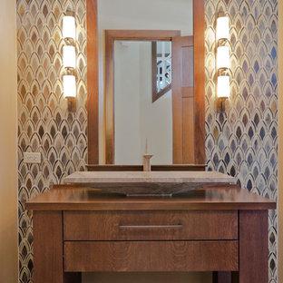 На фото: туалет среднего размера в современном стиле с фасадами островного типа, фасадами цвета дерева среднего тона, разноцветной плиткой, плиткой мозаикой, раковиной с несколькими смесителями, столешницей из дерева и коричневой столешницей с