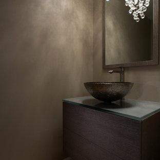 На фото: маленький туалет в стиле модернизм с плоскими фасадами, светлыми деревянными фасадами, светлым паркетным полом, настольной раковиной, серыми стенами, стеклянной столешницей и серой столешницей с