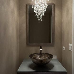 Aménagement d'un petit WC et toilettes moderne avec un placard à porte plane, des portes de placard en bois clair, un mur beige, une vasque, un plan de toilette en verre et un plan de toilette gris.