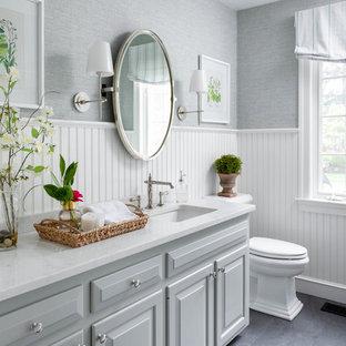 ボストンの中くらいのトラディショナルスタイルのおしゃれなトイレ・洗面所 (レイズドパネル扉のキャビネット、グレーのキャビネット、グレーの壁、アンダーカウンター洗面器、グレーの床、白い洗面カウンター) の写真