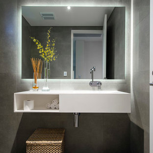 Inspiration for a large contemporary cloakroom in Perth with a wall-mounted sink, white cabinets, solid surface worktops, a one-piece toilet, grey tiles, slate flooring, grey walls and open cabinets.