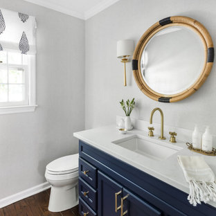 Traditional cloakroom in New York with recessed-panel cabinets, blue cabinets, grey walls, dark hardwood flooring, a submerged sink, brown floors, white worktops and a built in vanity unit.