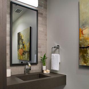 Exemple d'un WC et toilettes tendance avec un carrelage gris, un carrelage de pierre, un mur gris, un plan de toilette en béton et un lavabo intégré.