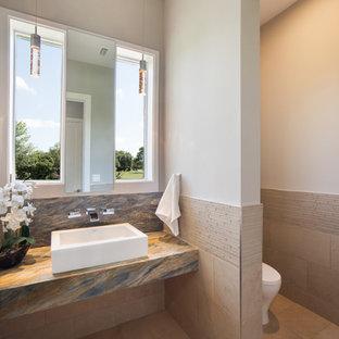 На фото: туалеты среднего размера в современном стиле с унитазом-моноблоком, бежевой плиткой, коричневой плиткой, удлиненной плиткой, серыми стенами и настольной раковиной