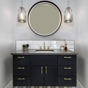 Cette photo montre un WC et toilettes chic de taille moyenne avec un placard à porte plane, des portes de placard bleues, un carrelage blanc, un carrelage métro, un mur gris, un sol en carreaux de ciment, un lavabo encastré, un plan de toilette en quartz modifié, un sol bleu et un plan de toilette gris.