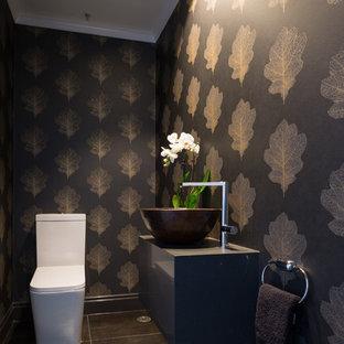 Esempio di un bagno di servizio minimal di medie dimensioni con ante grigie, WC monopezzo, pareti nere, pavimento in gres porcellanato, lavabo a bacinella, top in quarzo composito e pavimento nero
