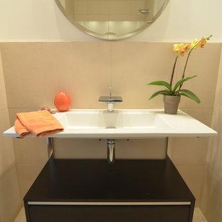 На фото: маленький туалет в стиле ретро с коричневыми фасадами, раздельным унитазом, бежевой плиткой, плиткой из известняка, белыми стенами, полом из галечной плитки, столешницей из искусственного камня и бежевым полом