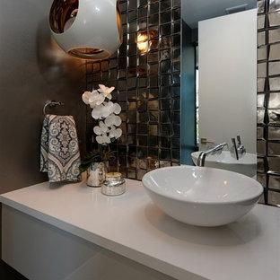 На фото: туалет среднего размера в современном стиле с плоскими фасадами, белыми фасадами, унитазом-моноблоком, бежевой плиткой, стеклянной плиткой, коричневыми стенами, полом из цементной плитки, настольной раковиной, столешницей из кварцита и серым полом с