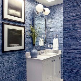Cette image montre un WC et toilettes marin avec un placard avec porte à panneau encastré, des portes de placard blanches, un mur bleu, un sol en carrelage de terre cuite, un lavabo encastré, un sol multicolore et un plan de toilette blanc.