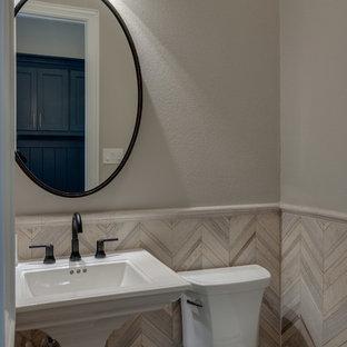Foto di un piccolo bagno di servizio classico con WC a due pezzi, piastrelle beige, piastrelle di pietra calcarea, pareti beige, pavimento in legno massello medio, lavabo a colonna e pavimento marrone