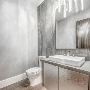 На фото: большой туалет в современном стиле с стеклянными фасадами, серыми фасадами, унитазом-моноблоком, разноцветной плиткой, керамогранитной плиткой, серыми стенами, паркетным полом среднего тона, настольной раковиной, столешницей из кварцита, коричневым полом и серой столешницей
