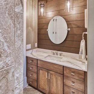 他の地域の中サイズのラスティックスタイルのおしゃれなトイレ・洗面所 (シェーカースタイル扉のキャビネット、中間色木目調キャビネット、一体型トイレ、ベージュの壁、アンダーカウンター洗面器、グレーの床、白い洗面カウンター) の写真