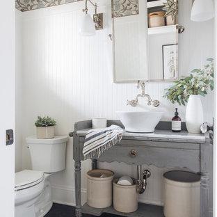 Immagine di un bagno di servizio tradizionale con consolle stile comò, ante grigie, WC a due pezzi, pareti multicolore, lavabo a bacinella, pavimento nero e top bianco