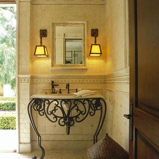 На фото: туалет в классическом стиле с монолитной раковиной, фасадами островного типа, бежевой плиткой, плиткой из известняка и бежевой столешницей с