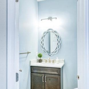 Imagen de aseo clásico renovado, pequeño, con armarios con rebordes decorativos, puertas de armario con efecto envejecido, sanitario de dos piezas, paredes azules, suelo de madera clara, lavabo bajoencimera, encimera de cuarcita, suelo marrón y encimeras blancas