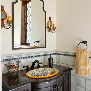 Идея дизайна: туалет в средиземноморском стиле с накладной раковиной, фасадами островного типа, темными деревянными фасадами, белыми стенами и синей плиткой