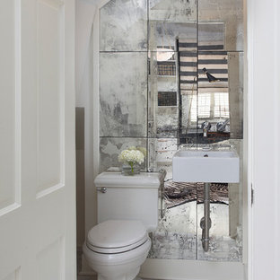 Inspiration for a small contemporary mirror tile powder room remodel in New Orleans with a wall-mount sink and white walls