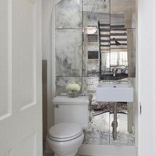 На фото: маленький туалет в современном стиле с подвесной раковиной, зеркальной плиткой и белыми стенами с