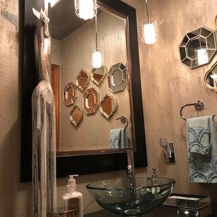 На фото: туалет среднего размера в современном стиле с стеклянными фасадами, черными фасадами, раздельным унитазом, серой плиткой, стеклянной плиткой, серыми стенами, полом из керамической плитки, настольной раковиной, столешницей из гранита и бежевым полом с