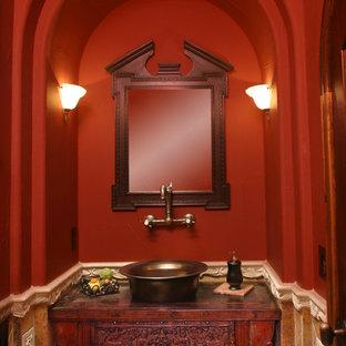 Imagen de aseo ecléctico, pequeño, con lavabo sobreencimera, armarios tipo mueble, puertas de armario de madera oscura, encimera de madera, baldosas y/o azulejos marrones, paredes rojas y encimeras rojas