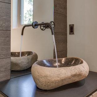 Inspiration pour un petit WC et toilettes minimaliste avec un placard à porte plane, des portes de placard marrons, un WC à poser, un carrelage marron, des carreaux de porcelaine, un mur blanc, un sol en carrelage de porcelaine, une vasque et un plan de toilette en acier inoxydable.