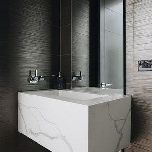 На фото: маленький туалет в современном стиле с инсталляцией, разноцветной плиткой, керамогранитной плиткой, светлым паркетным полом, подвесной раковиной, столешницей из искусственного кварца и белой столешницей с
