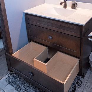ミネアポリスの大きいラスティックスタイルのおしゃれなトイレ・洗面所 (シェーカースタイル扉のキャビネット、濃色木目調キャビネット、分離型トイレ、グレーの壁、磁器タイルの床、一体型シンク、大理石の洗面台、ベージュの床) の写真