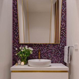 Cette image montre des WC et toilettes design de taille moyenne avec un placard à porte plane, des portes de placard blanches, un carrelage multicolore, carrelage en mosaïque, un mur violet, un sol en carrelage de céramique, une vasque, un plan de toilette en quartz modifié et un sol beige.