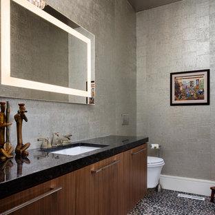 Moderne Gästetoilette mit flächenbündigen Schrankfronten, dunklen Holzschränken, grauer Wandfarbe, Kiesel-Bodenfliesen, Unterbauwaschbecken, buntem Boden und schwarzer Waschtischplatte in Kansas City