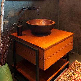 Aménagement d'un WC et toilettes craftsman de taille moyenne avec un placard en trompe-l'oeil, des portes de placard oranges, un carrelage gris, des carreaux de porcelaine, un mur beige, un sol en carrelage de porcelaine, une vasque, un plan de toilette en bois et un sol gris.