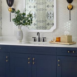 Réalisation d'un WC et toilettes tradition de taille moyenne avec un placard avec porte à panneau encastré, des portes de placard bleues, un carrelage blanc, des carreaux de céramique, un mur multicolore, un sol en ardoise, un lavabo posé, un plan de toilette en surface solide, un sol gris et un plan de toilette blanc.