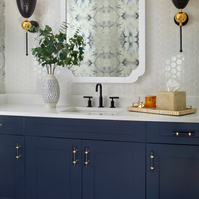 Mid-sized transitional white tile and ceramic tile slate floor and gray floor powder room photo in Denver with recessed-panel cabinets, blue cabinets, multicolored walls, a drop-in sink, solid surface countertops and white countertops
