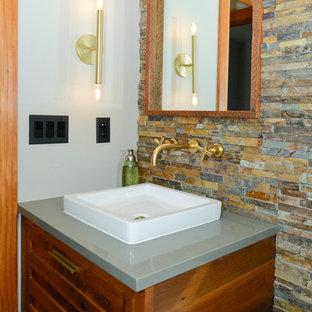 На фото: туалет среднего размера в стиле фьюжн с фасадами с филенкой типа жалюзи, фасадами цвета дерева среднего тона, унитазом-моноблоком, разноцветной плиткой, каменной плиткой, серыми стенами, полом из керамогранита, настольной раковиной, столешницей из искусственного кварца и серым полом с