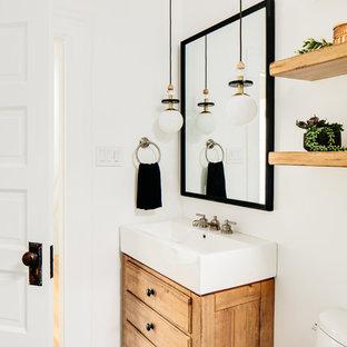 Idée de décoration pour un petit WC et toilettes nordique avec un placard en trompe-l'oeil, des portes de placard en bois brun, un mur blanc et un sol multicolore.