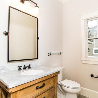 ワシントンD.C.のラスティックスタイルのおしゃれなトイレ・洗面所 (家具調キャビネット、淡色木目調キャビネット、分離型トイレ、モザイクタイル、御影石の洗面台、グレーの床、白い洗面カウンター) の写真