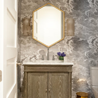 Small traditional cloakroom in Detroit with freestanding cabinets, a submerged sink, beige floors, white worktops, medium wood cabinets, a one-piece toilet, multi-coloured walls, porcelain flooring and marble worktops.