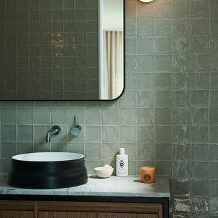 Стильный дизайн: туалет в современном стиле с плоскими фасадами, фасадами цвета дерева среднего тона, серой плиткой, серыми стенами, настольной раковиной, мраморной столешницей и белой столешницей - последний тренд
